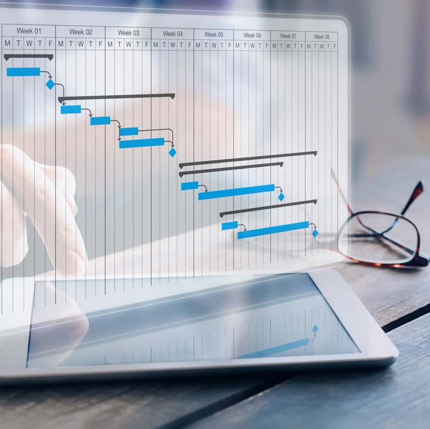 Project manager updating progress and deliverables milestones schedule on gantt chart planning with digital tablet computer, professional planner in office