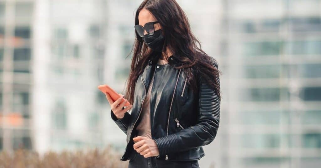 Mulher segurando celular de máscara