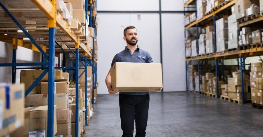 Homem segurando caixa em depósito de e-commerce