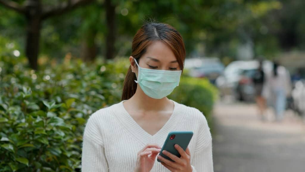 Novo Consumidor (mulher com máscara usando o celular)